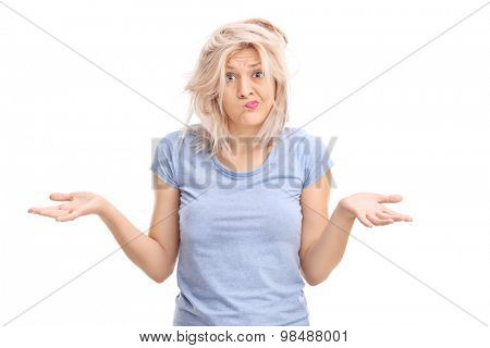 Confused blond girl with a messy hair gesturing with her hands and looking at the camera isolated on white background