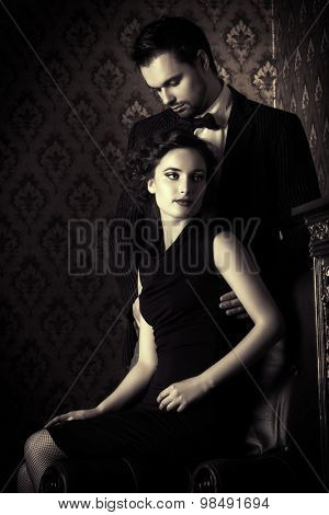Black-and-white photo of a beautiful couple in elegant evening clothes in classic vintage apartments. Glamour, fashion. Love concept.