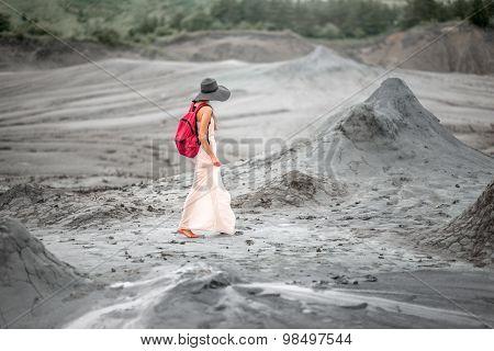 Female traveler walking near mud volcanoes