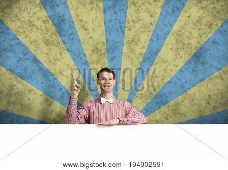 Young funny guy in checked shirt with banner pointing with finger up