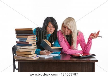 Two girlfriends of the student prepare for examination, sitting at a table on a white background.