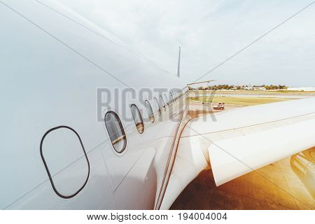 Wide angle view of modern white airplane fuselage with row of windows and part of wing staying on maintenance in airport of Male on sunny day with staff car passing by in background
