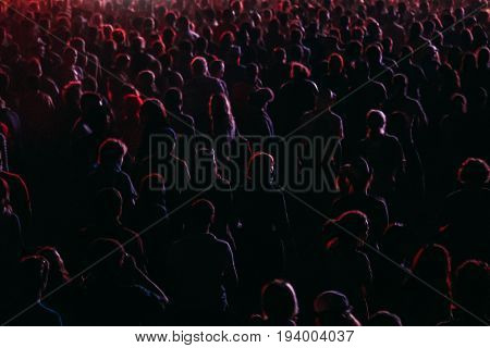 Crowd in a colorful lights of open air festival. silhouettes of night party