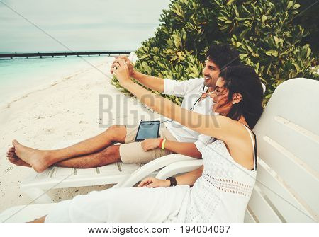 Smiling handsome adult man with digital tablet and his beautiful laughing female friend making joint selfie while having rest on deck chair in front of Indian ocean on Maldives resort