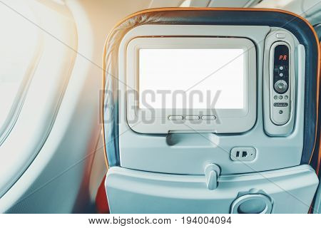 Empty white mock-up of aircraft multimedia screen with remote control close-up view of blank placeholder of airplane monitor filled with solid white in passenger seat multiple buttons and sockets