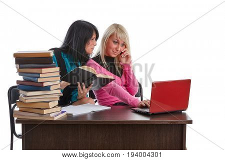 Two girlfriends of the student prepare for examination, sitting at a desk on a white background.