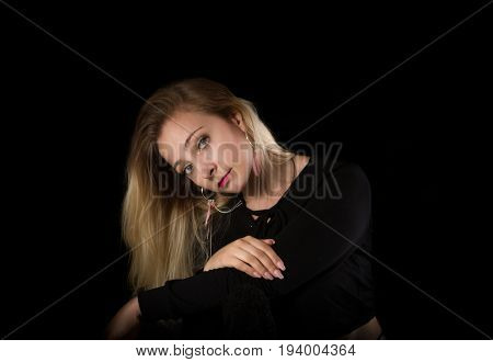 Portrait of a smiling woman on black background.