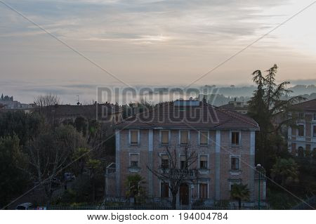 Italy Siena - December 26 2016: the view of typical old building in Siena at sunset light and green trees in fog on background on December 26 2016 in Siena Tuscany Italy.