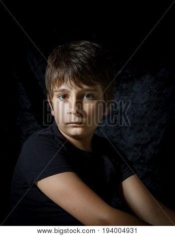 portrait of teen boy on black background