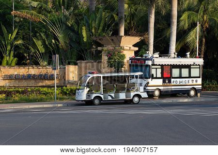 Sanya Hainan China April 24 2017 - An electric armored Chinese police bus and an 8-seater electric car are standing at the corner of the intersection.