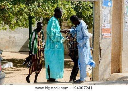 TOUBA, SENEGAL - APR 26, 2017: Unidentified Senegalese two men in traditional long clothes talk about somethng in the Great Mosque of Touba, the home of the Mouride Brotherhood