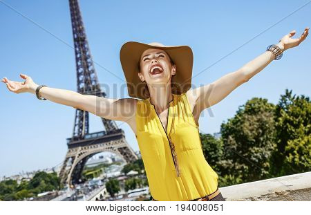 Smiling Young Woman Rejoicing In Front Of Eiffel Tower In Paris