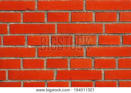 A red brick wall creates a boundary between borders.