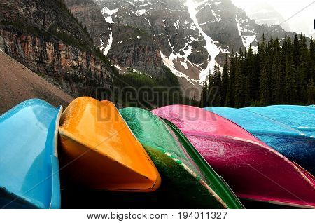 Colorful canoes on dry dock waiting for tourists to canoe on the lake.