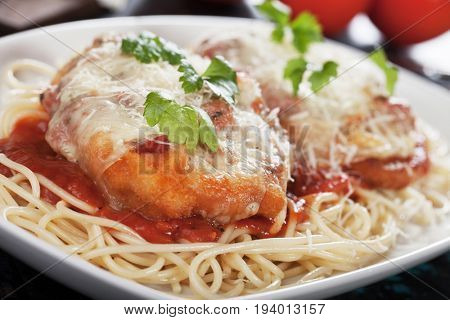 Italian chicken parmesan with melted cheese and tomato sauce served over spaghetti pasta