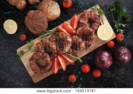 Grilled bacon rings on wooden board with lemon and tomato slices