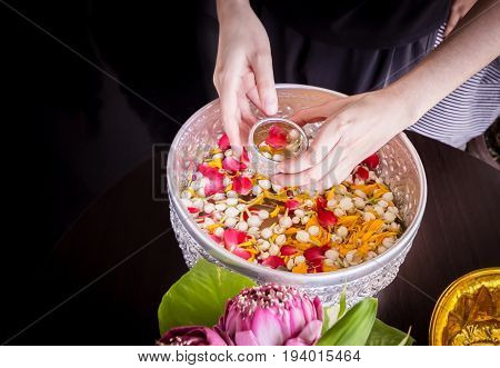 Women hand holding jasmine and rose leaf in bowl for bless adults Thai traditional for Mother's day and Father's day in thailand.