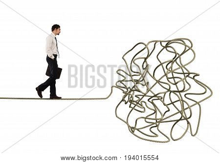 Problem and difficulty concept with a businessman who walk on a tangled rope