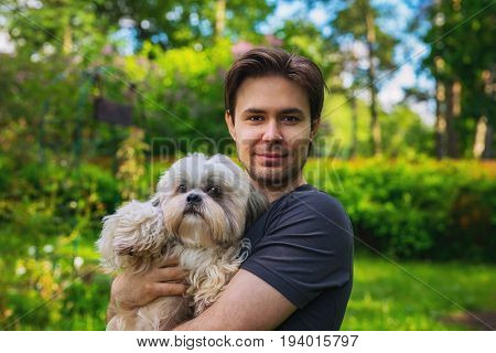 Young man with shih tzu dog portrait in summer garden. Love and care concept.