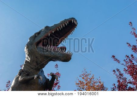 Dinosaur: Aggressive T-Rex against blue sky background