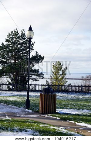 A street lamp and a trash can stand side by side in Sunset Park in Petoskey, Michigan during November.