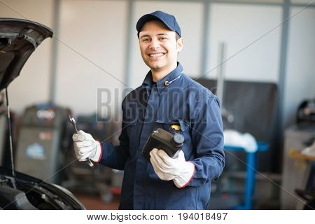 Portrait of an auto mechanicin front of a car in his garage