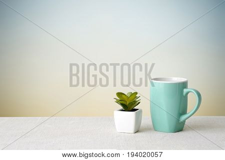 Green coffee cup on sack tablecloth over green cement wall background with copy space for text product display montage