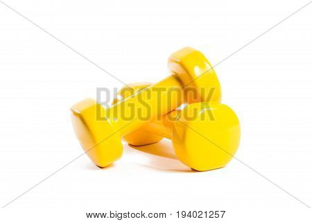 Two yellow dumbbells on an isolated background In a random order