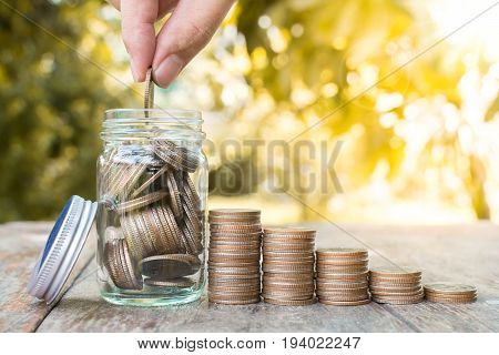 Hand putting coin stack in jar with blurred background and green leaf Save money and investment concept