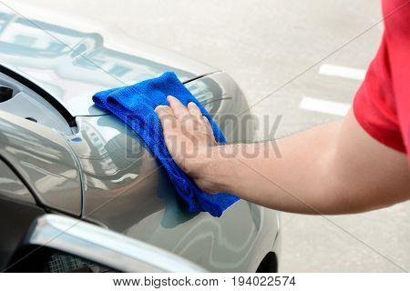 Hand rubbing and polishing car with microfiber cloth