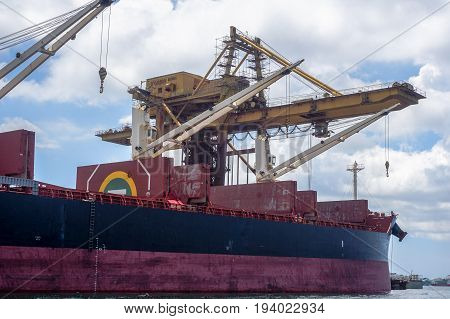 Labuan,Malaysia-June 12,2017:Huge cranes unloading iron ore from a bulk carrier in Labuan terminal iron ore port,Malaysia.