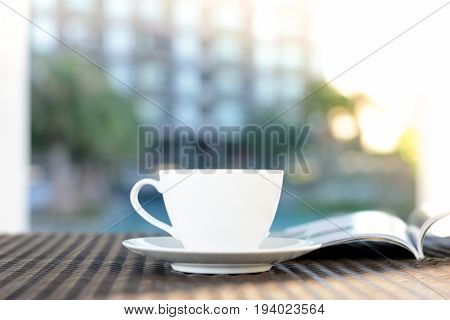 Blurred coffee cup with opened book on outdoor rattan table in the morning - chilling out in resort or hotel concept