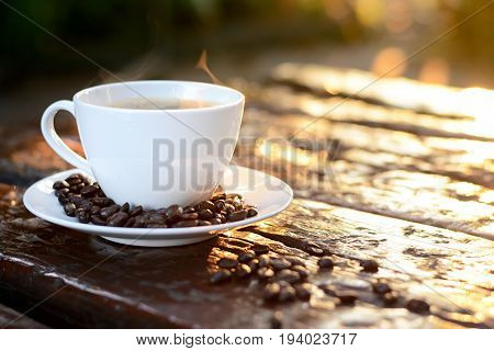 Hot coffee in the cup on old wood table with coffee beans - soft and blurred effect