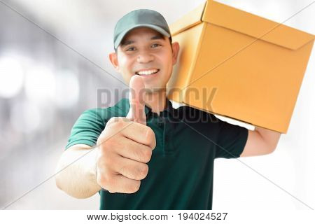 Deliveryman carrying a parcel box giving thumbs up