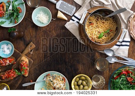 Frame of Italian pasta snacks end wine on a wooden table. Italian dinner table concept