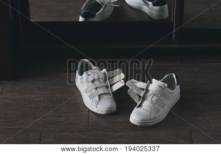 Pair of white shoes on velcro at home close-up