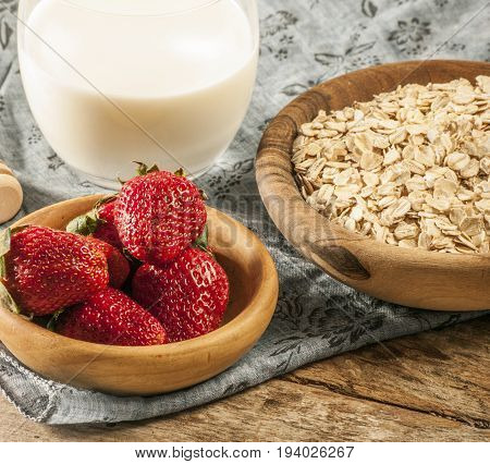 Healthy breakfast concept with oat flakes and fresh berries on rustic background. Food made of granola and musli. Healthy banana smoothie with blackberries, honey and milk.