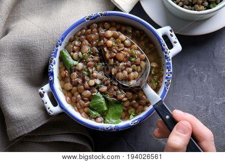 Hand of woman eating tasty lentil dish, closeup