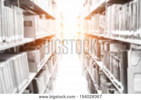 Abstract blurred background with many bookshelves in library at university.