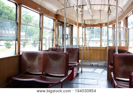 Interior of an tourism old vintage tram. Inside is empty, wooden red brown seats. Through the glass windows you can see the trees. Tourists attraction. Spring summer.