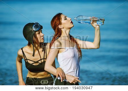 Girls on the beach with a bottle of water