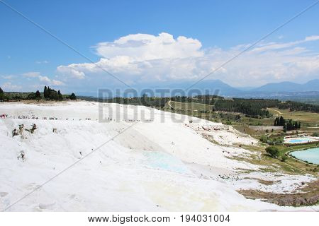 A view of the travertine from the side, many tourists on the most famous tourist attraction of Turkey, white calcium deposits on the background of the blue sky