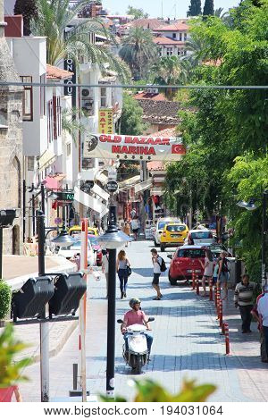 Antalya, Turkey - May 29 2017: Street view in old town - Kaleici, with pedestrians, tourists, cars and motorcyclists, vertical photo.