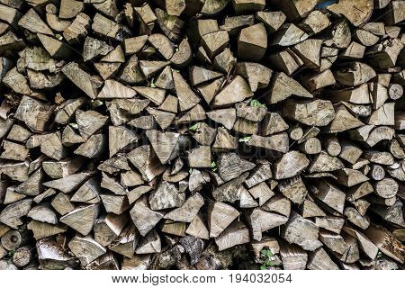 Abstract photo of a pile of natural wooden logs background dry chopped firewood logs ready for winter