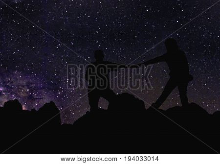 Silhouette of couple holding hands beneath the stars Milky Way and a lot of stars over the mountain at Wadi Rum desert. Sky at night in summer concept for space background traveling and romantic scenery.