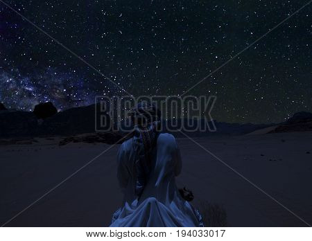 Silhouette of a person riding the camel beneath the stars Milky Way and a lot of stars over the mountain at Wadi Rum desert. Sky at night in summer concept for space background traveling and tranquil scenery.