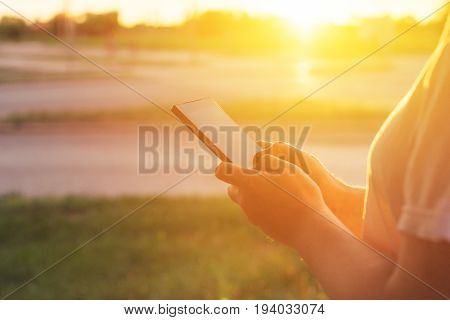 Using mobile phone on the street in morning woman typing message on smartphone during sunrise