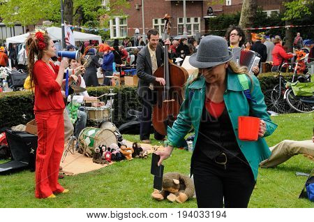 AMSTERDAM, NETHERLANDS - APRIL 30. Young People Celebrating Queensday in Amsterdam. Queensday is a popular annual festival celebrating the Queens Birthday.