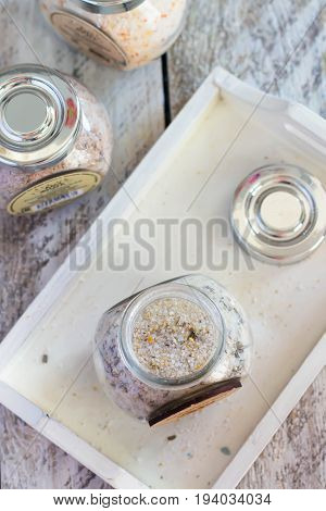 Top view of Sea Salt with additives Rosemary and lemon in jar on white wooden table background. Copy space
