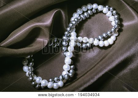 Necklaces of white and black pearls in the form of a sign of infinity on silk. Greeting card for the wedding International Women's Day March 8 Valentine's and Mother's Days.